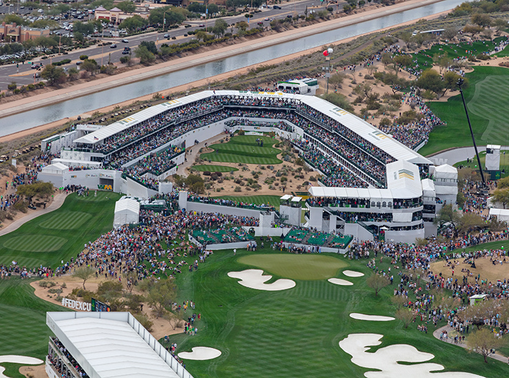 A crowds, in stadium seating, surround professional golfers on the 16th hole at the 2020 Waste Management Phoenix Open, Phoenix, AZ