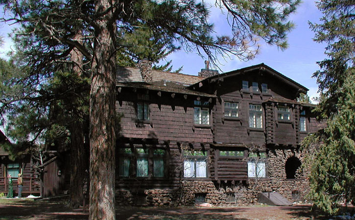 An Arts & Craft-style two-story mansion sits among a forest of pine trees.
