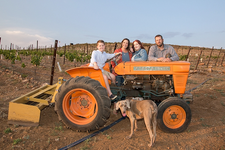 A family of four poses on an orange tractor in front of their vineyard with a brown dog.
