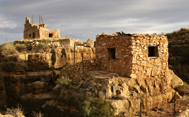 Stone ruins at Apache Death Cave stand alone and silent against a cloudy sky.