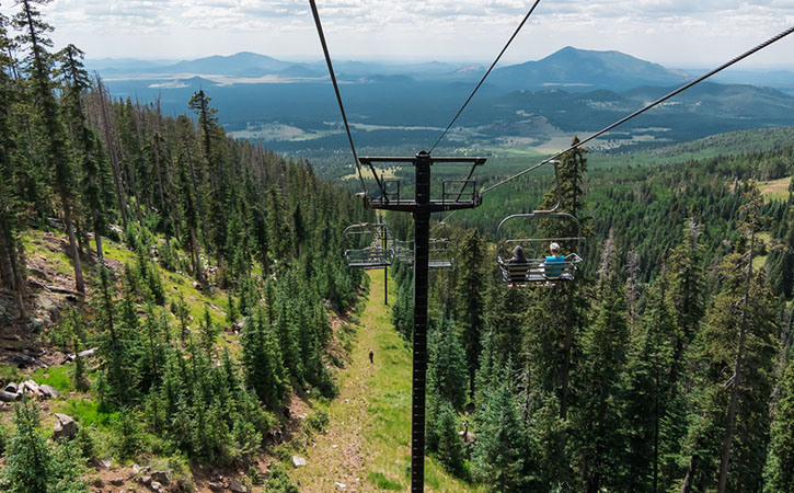 View of a chairlift as it descends into a grove of trees with a panoramic view of the mountains behind