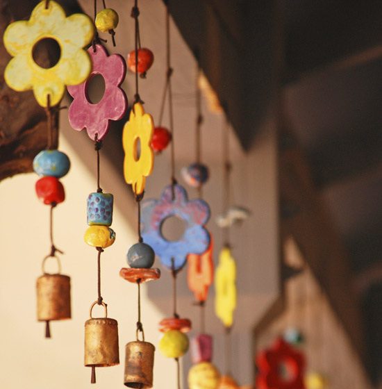 Several colorful, flower-shaped bell charms hang from a beam