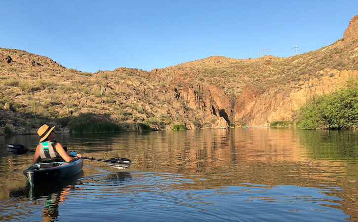 A kayaker looks up toward the sky while they drift on the water. In the distance, a canyon and other kayakers can be seen