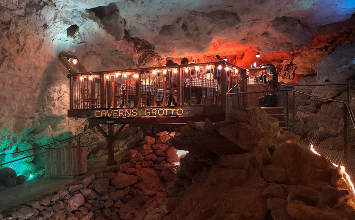 In a cave, a small deck built has been built with tables arranged for dining.