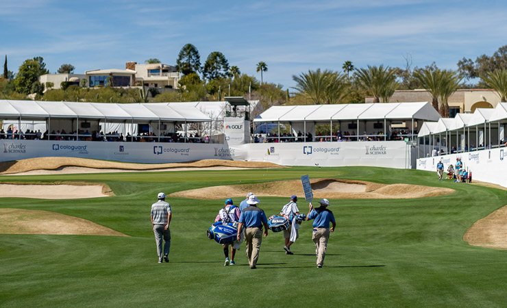 A group of men in golf clothes walk to the next hole on a golf course