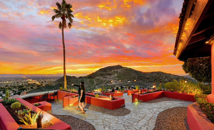 A couple stands on a patio overlooking a city. The sky is ablaze with a colorful sunset.