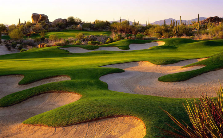 Sunset hits a green golf course that boasts myriad sand traps. It's and bordered by cactus and other desert foilage
