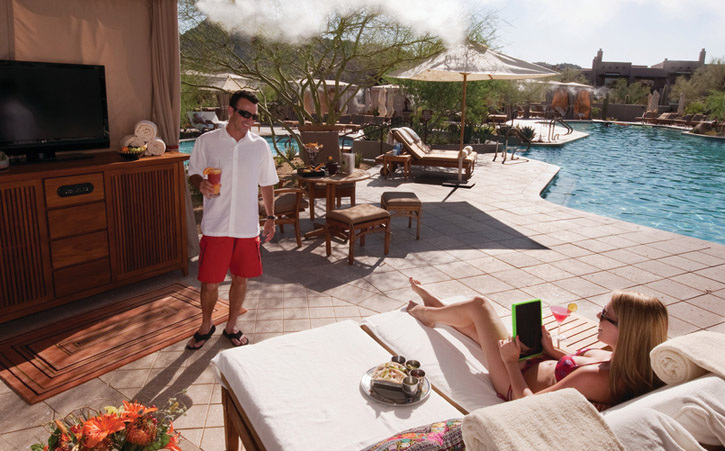 A man and woman relax in a private luxury cabana near a pool