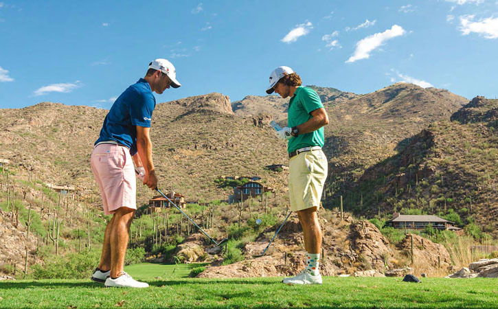 Two men face each other while one sets up a golf shot. In the distance are tall desert mountains.