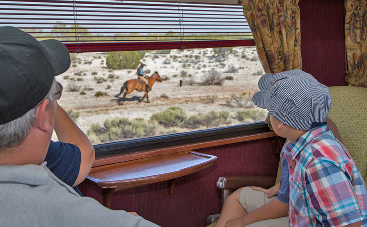 Two boys stare out the window of a train as a man on horseback rides by