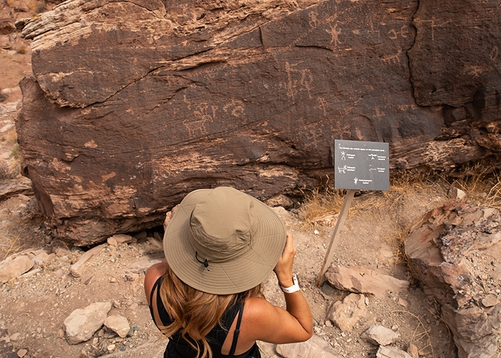 A woman in a hat takes a photo of petroglyphs at Homolovi State Park.