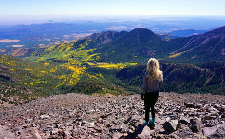 A woman stands atop a rocky overlook, looking down into a valley of green and yellow foliage surrounded by mountains