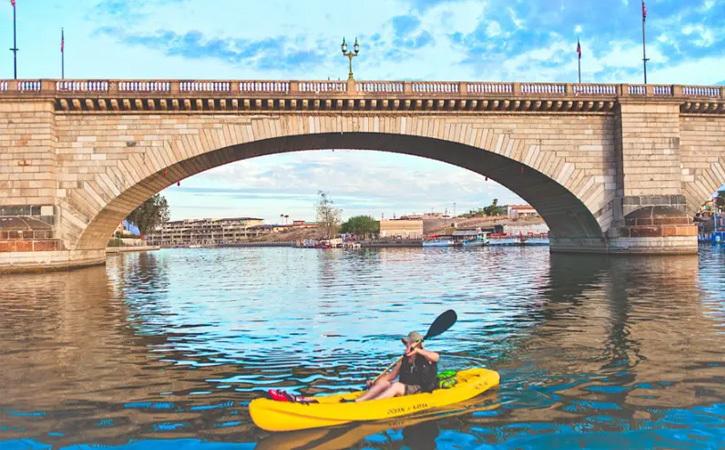 A man kayaks solo near the London Bridge in Lake Havasu City