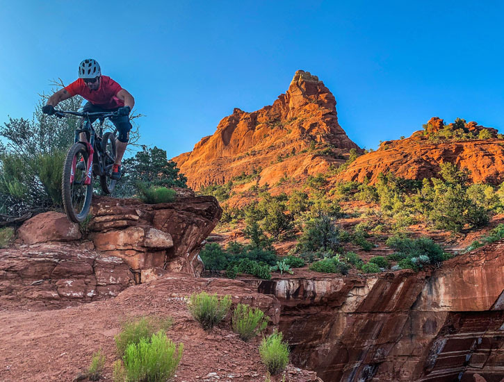 A mountain biker leaps over a rocky hill, a large mountain behind him