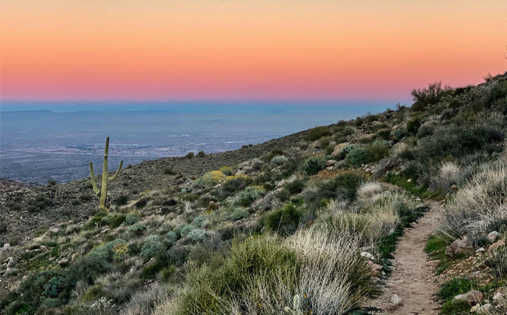 The sun sets over a narrow trail that curves around a desert mountain.
