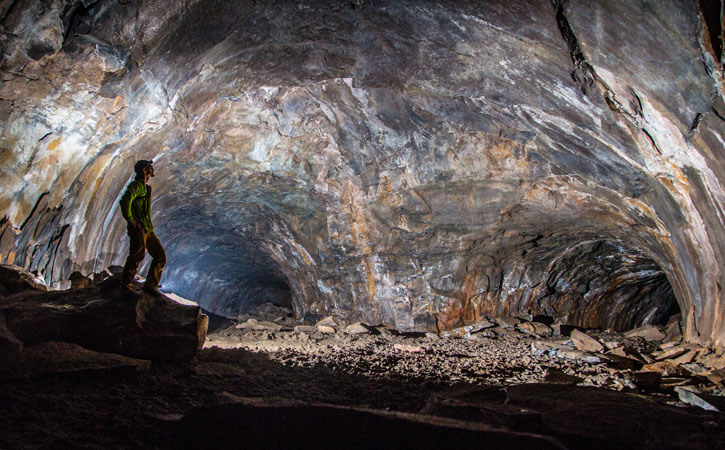 A man stands in shadow, a light illuminating a cave system with two tunnels