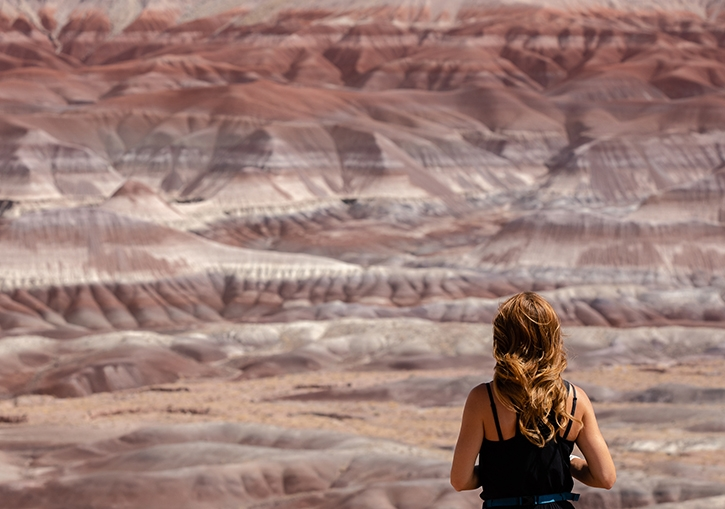 A woman admires the red and white sandstones of the Little Painted Desert County park with her back to the camera.