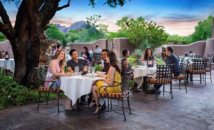A group of people sits at a table outdoors on a patio surrounded by trees.