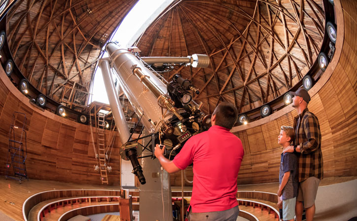 A man holds the controls of a large telescope, pointed toward the sky, as a father and son look on