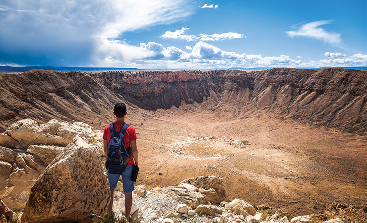 A man stands at the edge of a massive crater