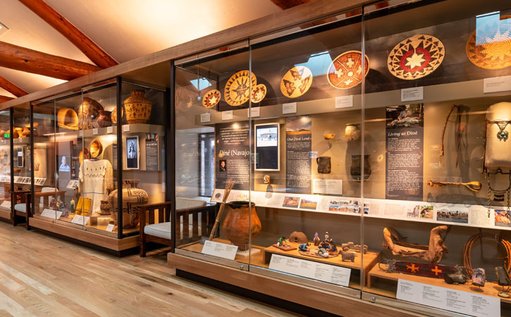 Woven baskets and traditional indigenous costumes are displayed in glass cases alongside other handcrafted goods and tools