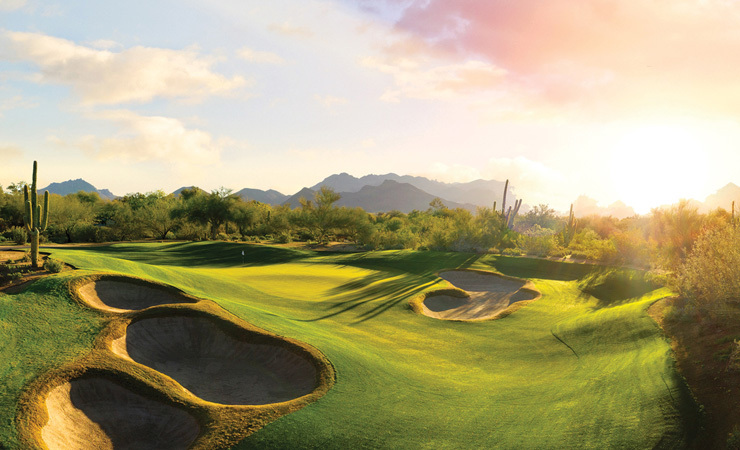 A rolling green golf course with sand traps under a desert sunset.