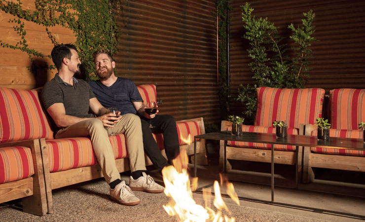 A couple sits on a low chair in a patio near a small campfire.