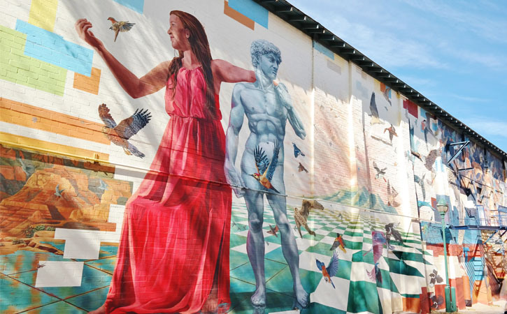 A large mural spans the length of a building's exterior wall. The image is a contemporary depiction of sound and performance.