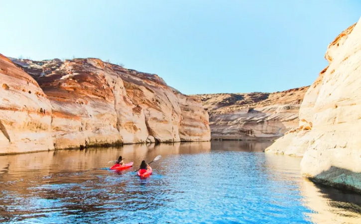 Two people kayak together on smooth waters without anyone nearby. They're flanked by canyon walls.