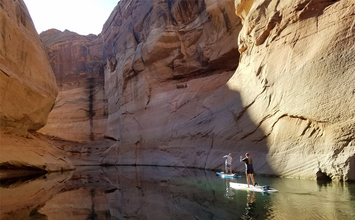 Two paddleboarders make their way through a canyon, partially covered in shadows