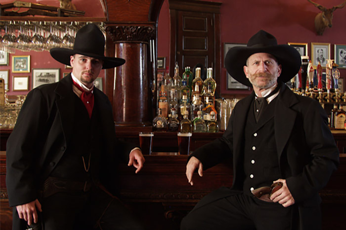 Two men in formal black, Old West clothing stand near a wooden bar