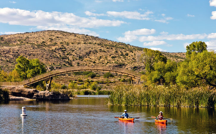 Kayakers sail along near an arched bridge that mimics the curves of the hills behind them.