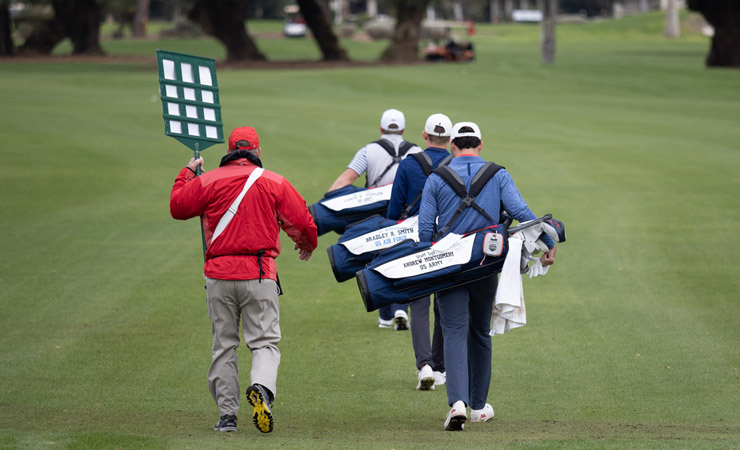 The backs of three golfers, each carrying a bag bearing the name of a fallen or severely injured US soldier