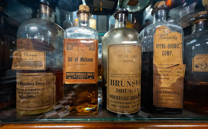 Four vintage bottles of medicine are lined up on a shelf, with yellow, peeling labels