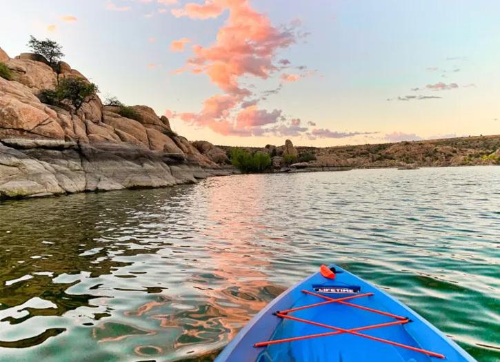 The tip of a blue kayak floats toward rocky hills of Prescott's Granite Dells