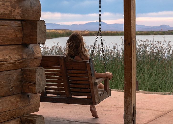 A woman sitting on a porch swing watching a sunset storm at Roper Lake State Park, from the deck of the Hummingbird Cabin