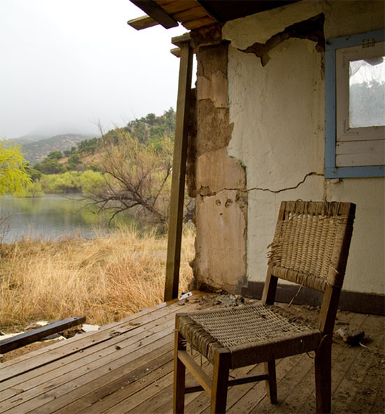 An old wicker chair sits alone in an abandoned building that has lost a wall. Outside are grasslands and a small creek