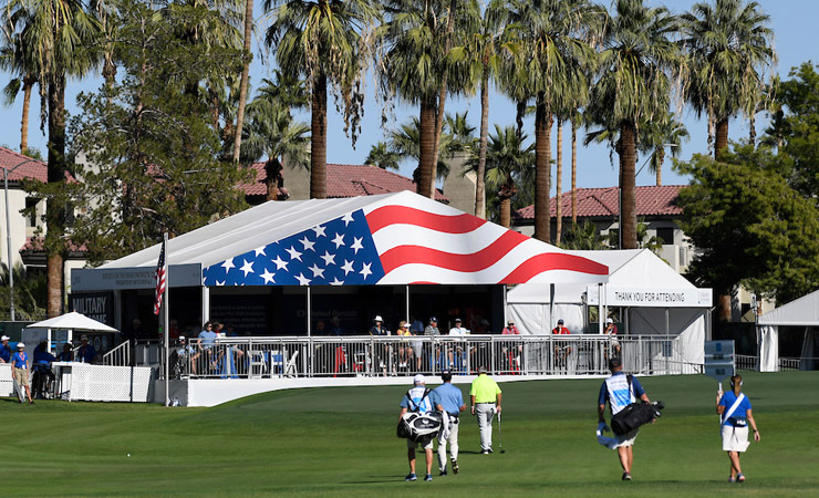 A tented outpost is decorated with the emblem of an American Flag. In the foreground, golfers walk to the next hole.