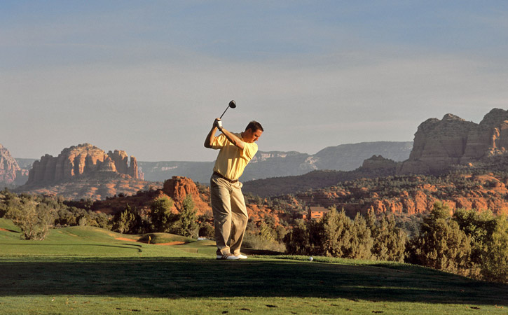 A man swings a golf club on a course set against the backdrop of Sedona's Red Rock State Park