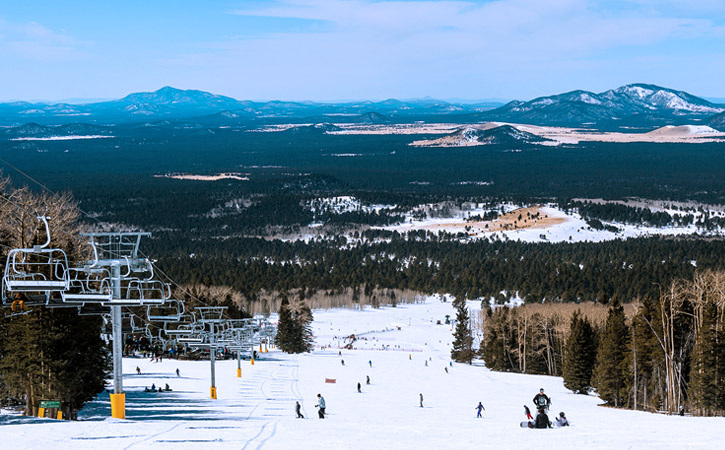 Guests at Arizona Snowbowl ski down a large snow-covered mountainside with a view of the San Francisco Peaks below