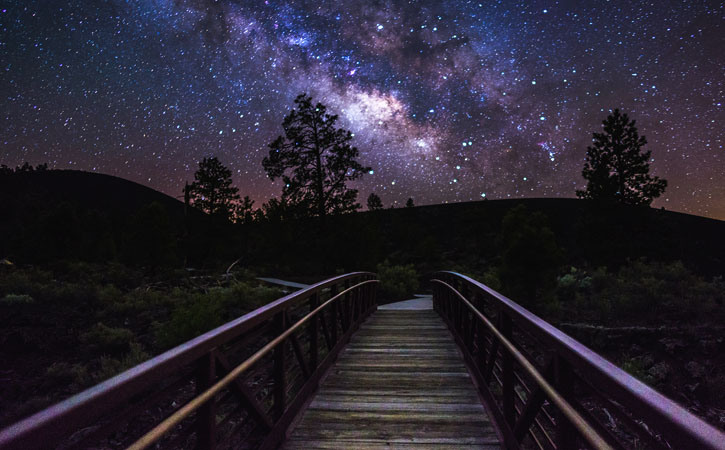 The Milky Way and the night sky can be seen in full view above a wooden path at night