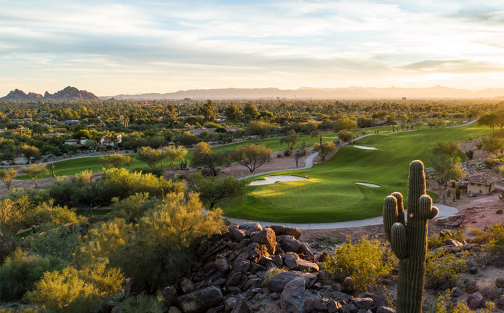 A green golf course is surrounded by saguaro cactus and mountains