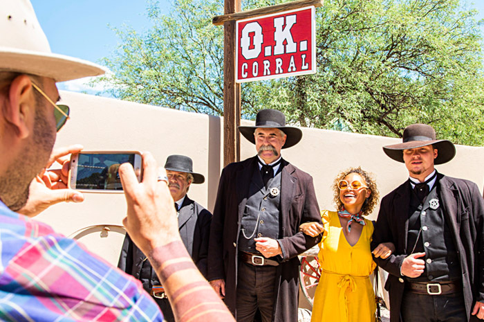 A woman in a yellow dress smiles as she poses with male actors in Old West costumes