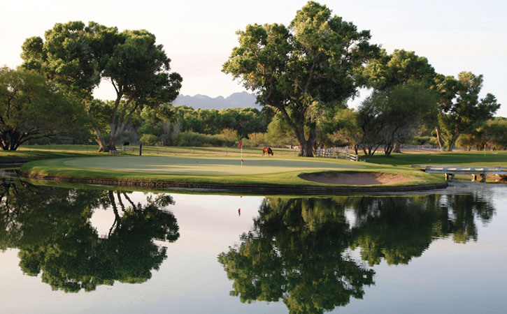 Large, green mesquite trees dot a green golf course that sits near a lake, mirroring the trees above