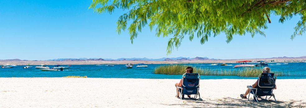 Two people lounge in chairs on the beach of Lake Havasu State Park as boats motor by