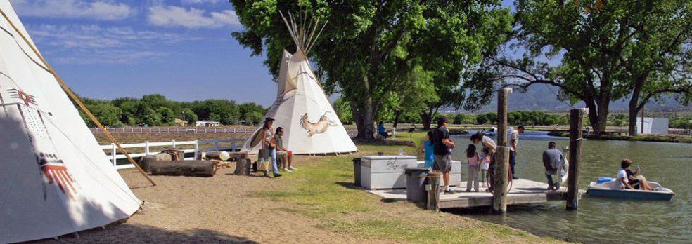 A group of family and friends play in the lake near the teepees and trees and Jackpot Ranch.