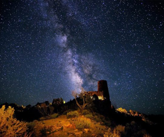 Mary Colter's watchtower at the Grand Canyon is illuminated from above by millions of stars and the Milky Way
