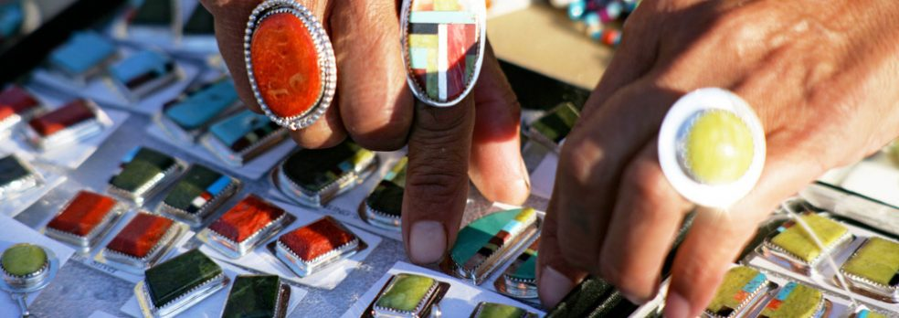 Close-up on the hands of a Yavapai woman, organizing her jewelry for sale.