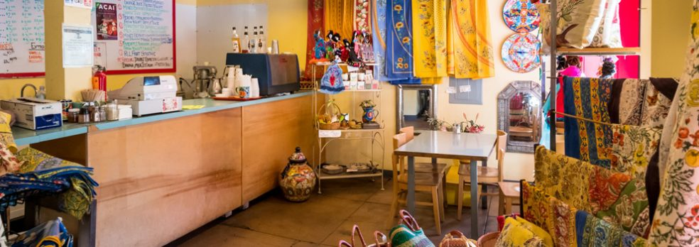 Imported world goods like blankets, dolls, and baskets line the walls near the cashier at High Desert Market and Cafe.