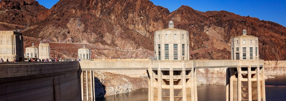 Visitors on the bridge of the Hoover Dam look out at the towers